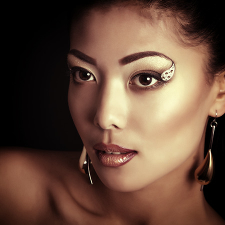 make up model: Young fresh luxury woman with golden makeup Stock Photo