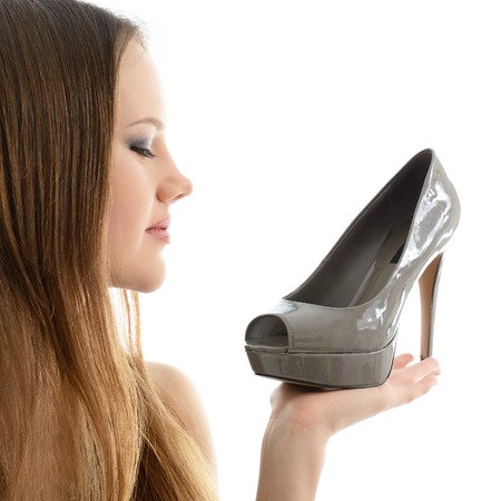 shoe model: Girl holding shoe in hand an looking with love on it, over white background.