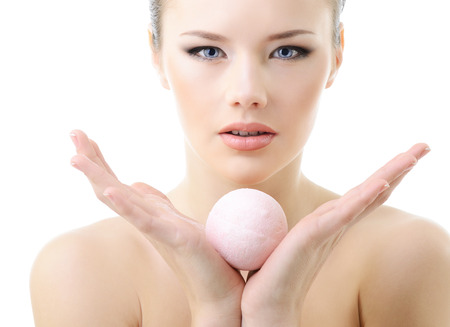Beautiful young woman with aroma soap bath ball, over white.