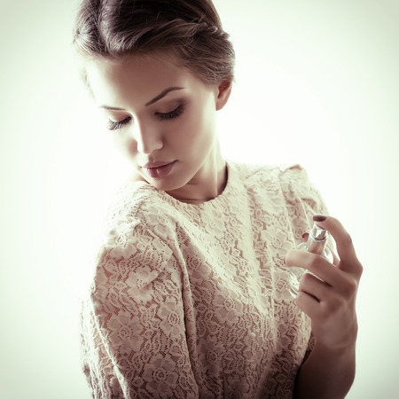 Girl with perfume, young beautiful woman holding bottle of perfume and smelling aroma, toned soft beige