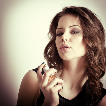Girl with perfume, young beautiful woman holding bottle of perfume and smelling aroma, toned soft beige. photo