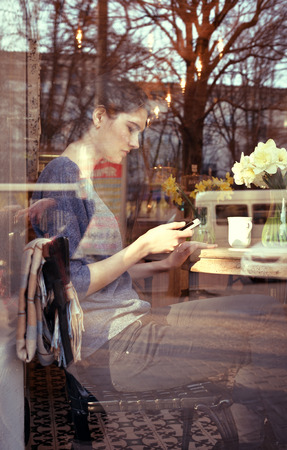 Young woman drinking coffee and use her smartphone sitting indoor in urban cafe. Cafe city lifestyle. Casual portrait of beautiful girl with spring flowers. Image toned. photo