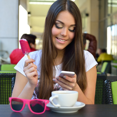 Beautiful cheerful teen girl eating icecream and using smartphone in outdoor cafe, urban teenager lifestyle. photo