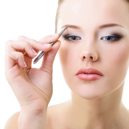 pinzas: Joven y bella mujer depilarse las cejas más de blanco Foto de archivo