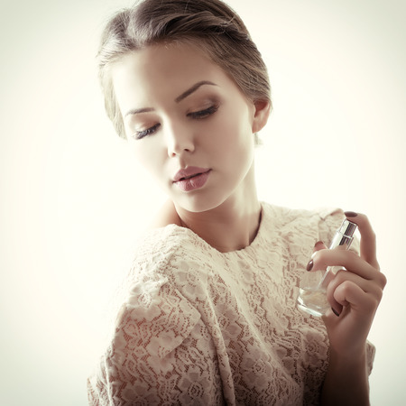 Girl with perfume, young beautiful woman holding bottle of perfume and smelling aroma, toned