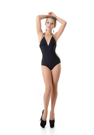 long legs: Sexy young woman posing in a black swimsuit full length isolated studio portrait, over white background