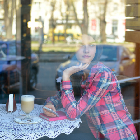 Young woman drinking coffee and use her smartphone sitting indoor in urban cafe. Cafe city lifestyle. Casual portrait of beautiful girl. Toned. photo