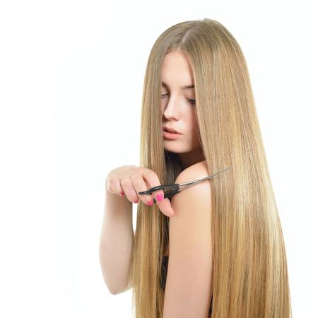 Haar. Schöne Frau, schnitt ihr mit einer Schere lange gesund glänzend glattes Haar. Haarpflege-Konzept.