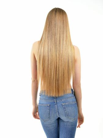 Dei capelli. Bella donna con lunghi capelli lisci sani e lucidi. Punto di vista posteriore della ragazza bionda in jeans su sfondo bianco. Capelli splendidi. La cura dei capelli.