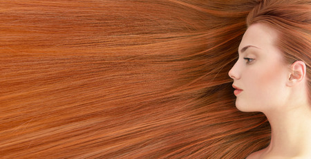 salon background: Red hair. Beautiful young woman with  long healthy hair. Stock Photo