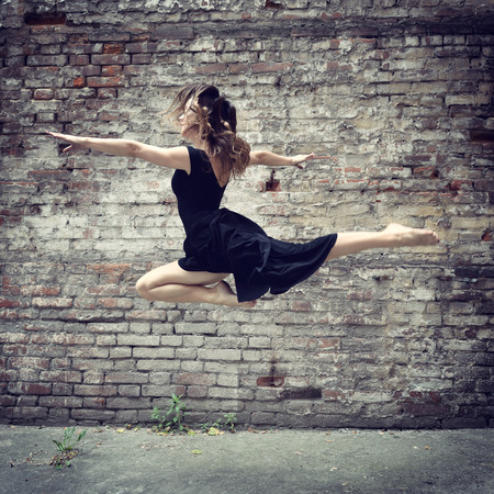 Attractive teen girl dancing outdoor against grunge bricks wall. Toned. photo