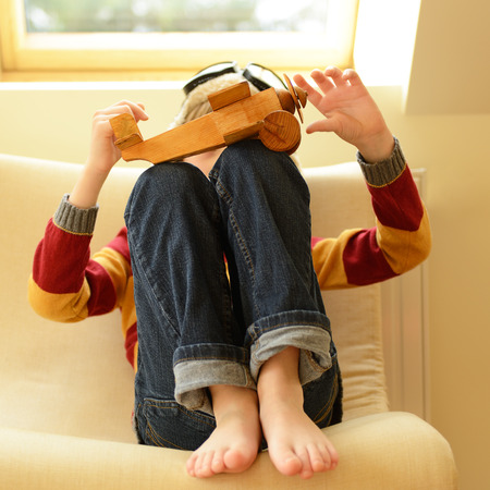airman: Little boy aviator dreaming and playing with wooden handmade toy plane at home