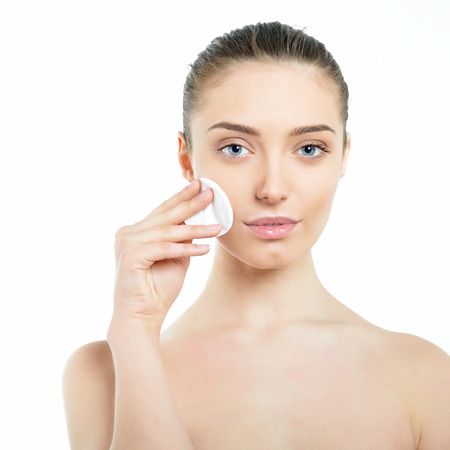 Beautiful fresh cheerful woman. Female face with perfect skin holding in hand cotton pad.
