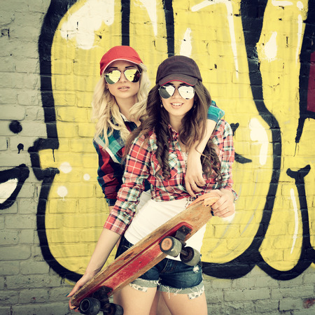 board shorts: Two teen girl friends having fun together with skate board. Outdoors, urban lifestyle. Toned. Stock Photo