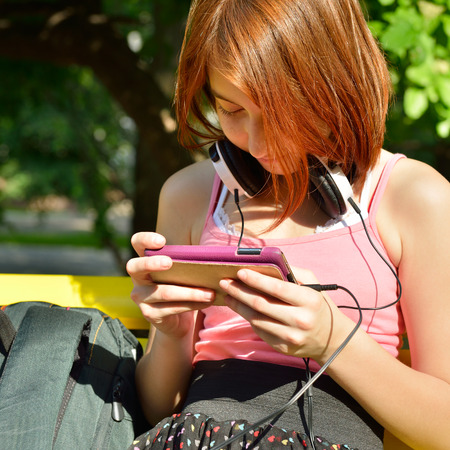 Teen girl have fun outdoor with smartphone. photo