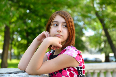 in low spirits: Young girl alone in park, face close up. Stock Photo