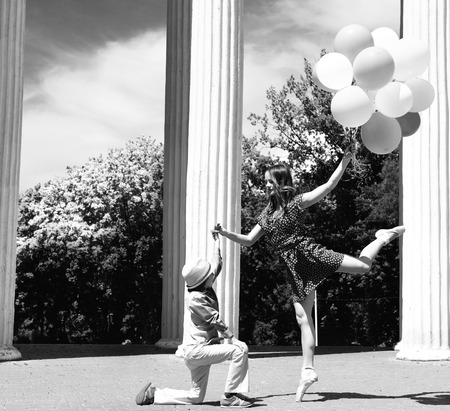 Elegant beautiful teen girl dancer in pointes posing outdoor with little boy holding colored ballons. Black and white. photo