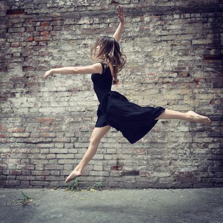 urban dance: Attractive teen girl dancing outdoor against grunge brics wall. Toned.