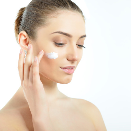 woman face cream: Beautiful young woman applying cream on her face. Girl with perfect skin over white. Stock Photo