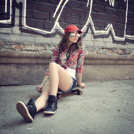 graffiti art: Portrait of beautiful teen girl sitting on skateboard over wall with abstract graffiti art. Urban outdoors, teenagers lifestyle. Toned.