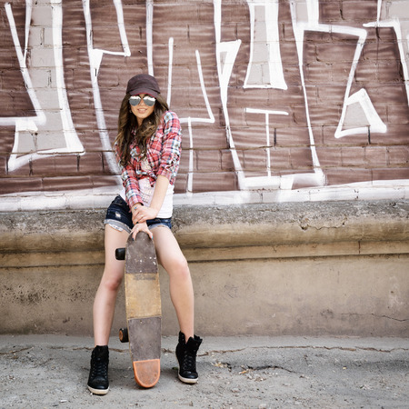graffiti art: Portrait of beautiful teen girl standing on skateboard over wall with abstract graffiti art. Urban outdoors, teenagers lifestyle. Toned. Stock Photo
