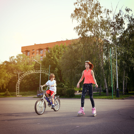 Teen girl on roller skates smiling and little boy bike on bicycle behind. Toned. photo