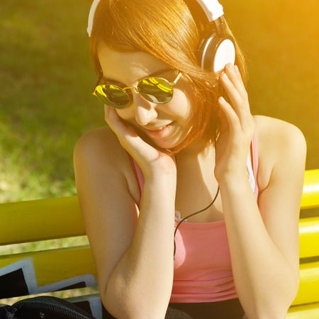 Young beautiful teen girl listening music outdoor with headphones.Toned. photo