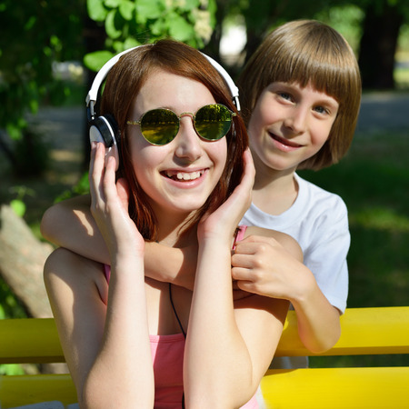 brothers and sisters: Boy and teen girl have fun outdoor in summer park. Happy children. Stock Photo