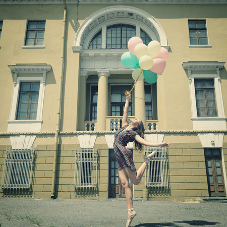 urban dance: Attractive teen girl dancing with ballons outdoor against old building. Vintage toned.