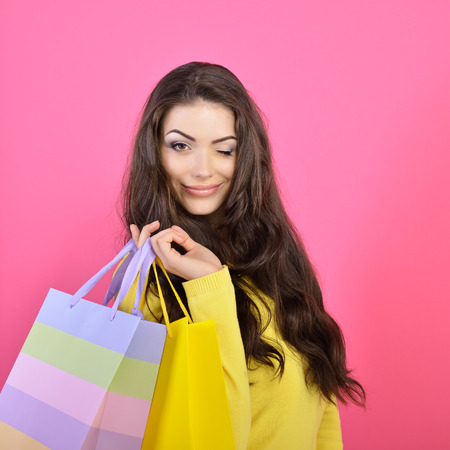 Shopping woman holding bags and gives a wink, isolated on pink studio background.  photo