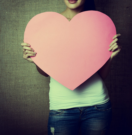 incognito: portrait of young woman holding pink heart incognito, love holiday valentine symbol over canvas background, toned Stock Photo