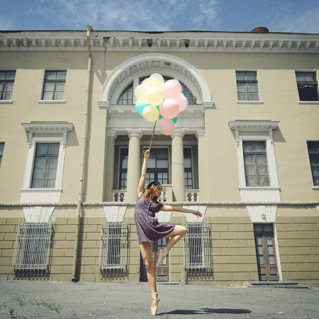 people in action: Attractive teen girl dancing with balloons outdoor against old building. Toned Stock Photo