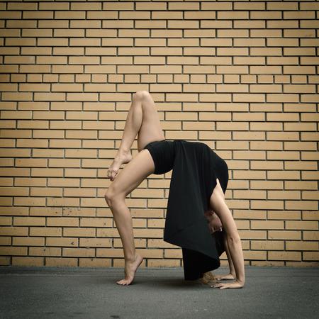 slender: Attractive teen girl dancing outdoor against brics wall. Toned. Stock Photo