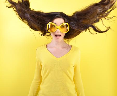 Örömteli izgatott meglepett fiatal nő, repülő haj és a nagy vicces poharak fölött sárga háttér.