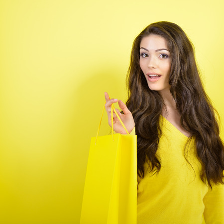 Shopping happy young woman holding bags over yellow studio background.  photo