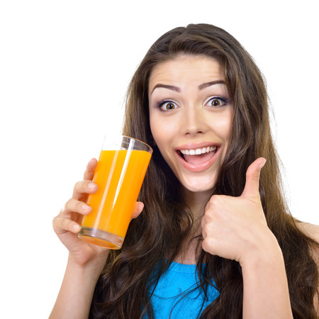 ady: Young cheerful woman drinks orange juice and showing tumb up over white.