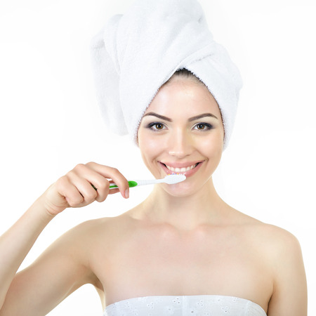 Young fresh cheerful woman with tooth-brush and bath towel over white. photo