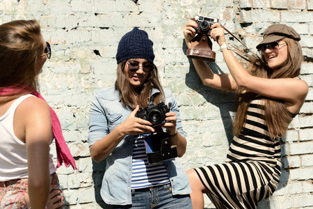 cool girl: Urban girls have fun with vintage photo cameras outdoor near grunge wall, filtered