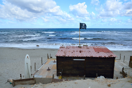 rovers: Beach surf hous with sea rovers flag with the Jolly Roger over storm sea Stock Photo
