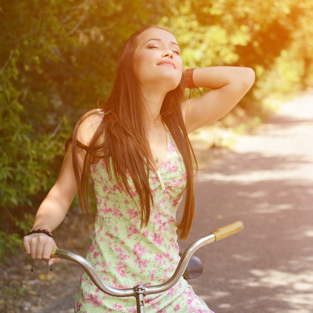 Happy smiling young beautiful woman with retro bicycle, summer outdoor, image toned