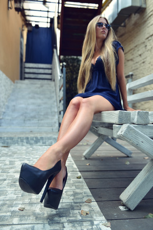 Long Legs Fashion Blonde Girl Sitting on Bench. Street Fashion. Urban Lifestyle. Young Beautiful Woman Walking Outdoor. Focus on Legs. Toned. photo