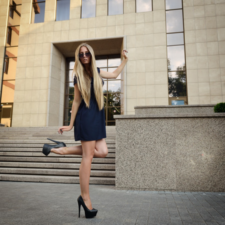 Fashion Blond Girl with Long Legs. Street Fashion. Urban Lifestyle. Young Beautiful Woman Walking Outdoor. photo