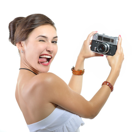 Beautiful girl takes her self picture with retro photo camera, over white. photo