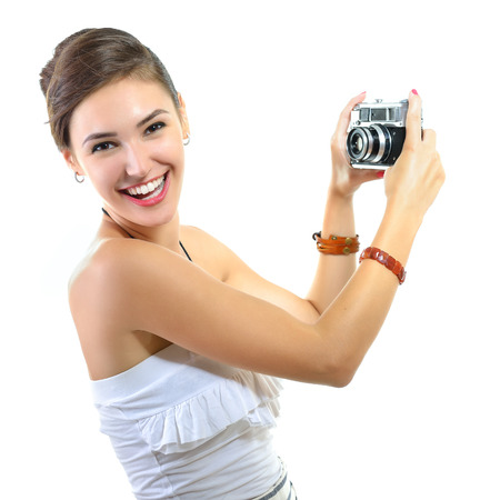 takes: Beautiful girl takes her self picture with retro photo camera, over white.