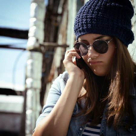 Teen girl calling smart phone outdoor. Teenage problem. Image toned and noise added. photo