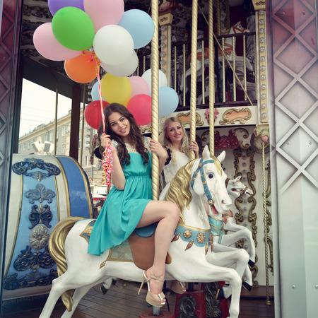 femme et cheval: Merry-go-round jeunes femmes jouant sur carrousel, tonique. Banque d'images