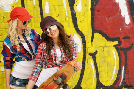 Two teen girl friends having fun together with skate board. Outdoors, urban lifestyle. Toned. photo