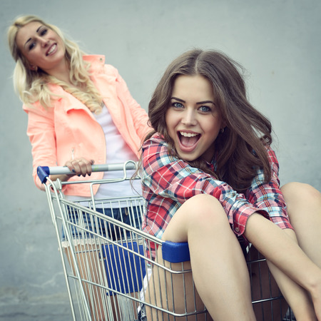Two happy beautiful teen girls driving shopping cart outdoor, Image toned and noise added. Stock Photo