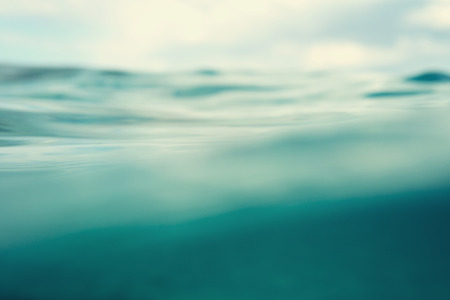 close up image: Water. Sea. Ocean, Wave close up. Nature background. Soft focus. Image toned and noise added.