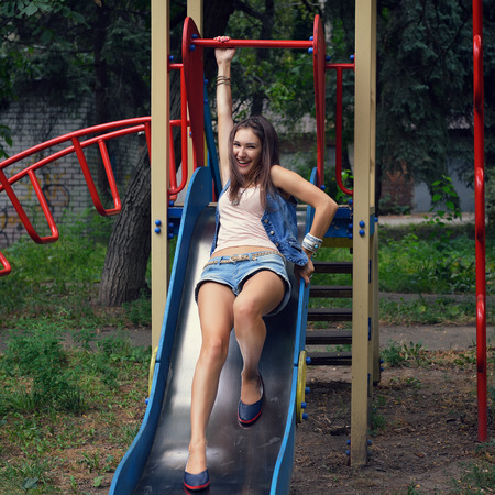 hillock: Happy teen girl has fun  on child hillock on playground. Outdoors. Image toned and noise added. Stock Photo
